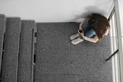 Adolescente turbato con lo smartphone che si siede sulla scala all'interno fotografia stock libera da diritti