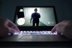 Adolescente u hombre joven que juega al videojuego de la acción o del crimen Imagen de archivo libre de regalías