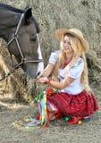 Adolescente ucraniano en caballo tradicional de las alimentaciones de la ropa Imagen de archivo libre de regalías