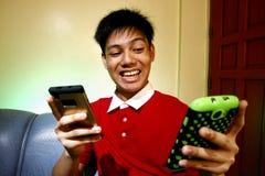 Adolescente usando dos smartphones Fotos de archivo