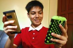 Adolescente usando dos smartphones Imagenes de archivo