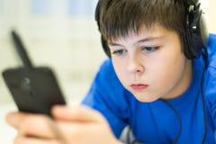 Adolescente usando el teléfono celular con los auriculares Fotos de archivo