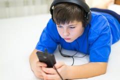 Adolescente usando el teléfono celular con los auriculares Imagenes de archivo