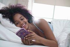 Adolescente usando el teléfono móvil para la charla en cama en casa Fotos de archivo
