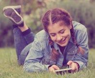 Adolescente usando la tableta digital mientras que miente en parque del verano Fotografía de archivo
