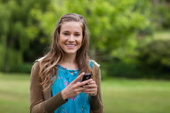Adolescente usando su teléfono móvil mientras que envía un texto Imágenes de archivo libres de regalías