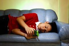 Adolescente usando un smartphone mientras que se acuesta en un sofá y una sonrisa Foto de archivo