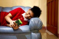 Adolescente usando un smartphone mientras que se acuesta en un sofá y una sonrisa Imagen de archivo libre de regalías