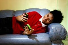 Adolescente usando un smartphone mientras que se acuesta en un sofá y una sonrisa Imagen de archivo