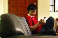 Adolescente usando un smartphone mientras que se sienta en el sofá Fotografía de archivo