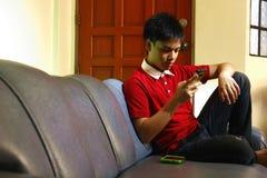 Adolescente usando un smartphone mientras que se sienta en el sofá Imagenes de archivo