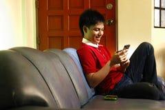 Adolescente usando un smartphone mientras que se sienta en el sofá y la sonrisa Foto de archivo libre de regalías