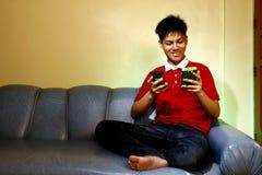 Adolescente usando un smartphone mientras que se sienta en el sofá y la sonrisa Fotos de archivo libres de regalías