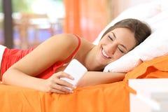Adolescente usando un teléfono elegante en la cama Fotos de archivo
