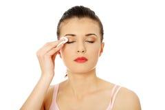 Adolescente usando una pista de algodón para quitar su maquillaje Foto de archivo libre de regalías