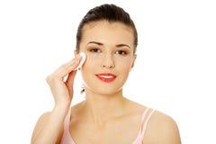 Adolescente usando una pista de algodón para quitar su maquillaje Imágenes de archivo libres de regalías