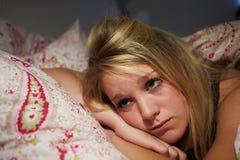 Adolescente éveillée dans le lit souffrant avec l'insomnie Image libre de droits