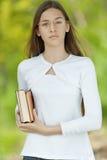 Adolescente vestido en blanco con los libros Fotos de archivo
