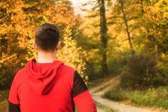 Adolescente vestido en caminar rojo de la sudadera al aire libre Imagen de archivo libre de regalías