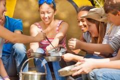Adolescente vierte la sopa en las placas metálicas para sus amigos Fotografía de archivo libre de regalías