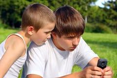 Adolescente y cabrito con el teléfono móvil Foto de archivo