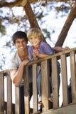 Adolescente y casa de Brother Playing In Tree junto Fotografía de archivo