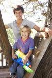 Adolescente y casa de Brother Playing In Tree junto Imagen de archivo