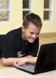 Adolescente y computadora portátil en suelo Imagenes de archivo