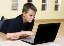 Adolescente y computadora portátil en suelo Imagen de archivo