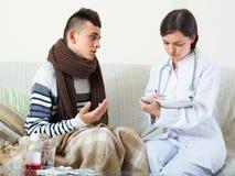 Adolescente y doctor en casa Foto de archivo libre de regalías