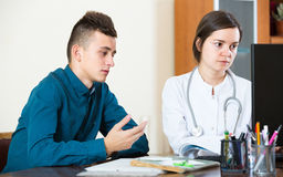 Adolescente y doctor en el escritorio en clínica Imagen de archivo libre de regalías