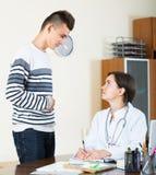Adolescente y doctor en el escritorio en clínica Imagenes de archivo
