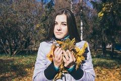 Adolescente y el brazado de hojas de otoño amarillas Fotografía de archivo