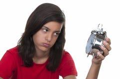 Adolescente y el reloj de alarma Fotos de archivo