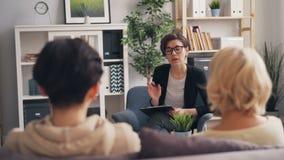 Adolescente y madre asesores de la familia del psicólogo acertado que hablan en oficina almacen de video