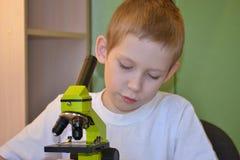 Adolescente y microscopio Foto de archivo libre de regalías