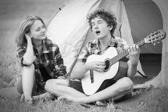 Adolescente y muchacha cerca de la tienda que toca una guitarra al aire libre Imagenes de archivo