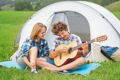 Adolescente y muchacha cerca de la tienda que toca una guitarra al aire libre Imágenes de archivo libres de regalías