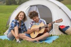 Adolescente y muchacha cerca de la tienda que toca una guitarra al aire libre Foto de archivo