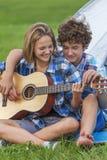 Adolescente y muchacha cerca de la tienda que toca una guitarra al aire libre Imagen de archivo