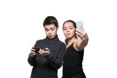 Adolescente y muchacha con su teléfono elegante Imagenes de archivo