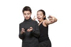 Adolescente y muchacha con su teléfono elegante Imagen de archivo libre de regalías