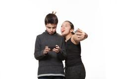 Adolescente y muchacha con su teléfono elegante Fotos de archivo libres de regalías