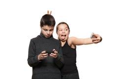Adolescente y muchacha con su teléfono elegante Fotos de archivo