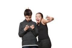 Adolescente y muchacha con su teléfono elegante Foto de archivo libre de regalías