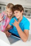 Adolescente y muchacha en la computadora portátil Imagen de archivo libre de regalías