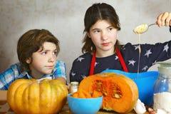 Adolescente y muchacha que cocinan el pastel de calabaza Fotos de archivo libres de regalías