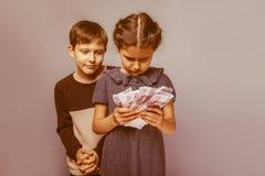 Adolescente y muchacha que llevan a cabo cuentas de dinero en el suyo Imagen de archivo
