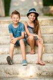 Adolescente y muchacha que se sientan en las escaleras en parque Imágenes de archivo libres de regalías