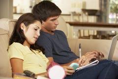 Adolescente y muchacha que se sientan en Sofa At Home Doing Homework que usa el ordenador portátil mientras que sostiene el teléf Fotografía de archivo